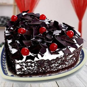 Heart shape black forest cake topping with cherries